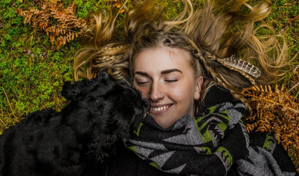 Nainen makaa maassa, hymyilee ja koira on hänen naaman vieressä