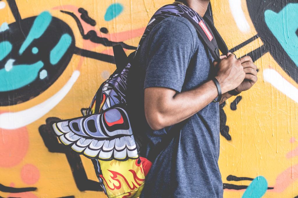 En ung person med ryggsäck på ryggen står framför en graffitivägg