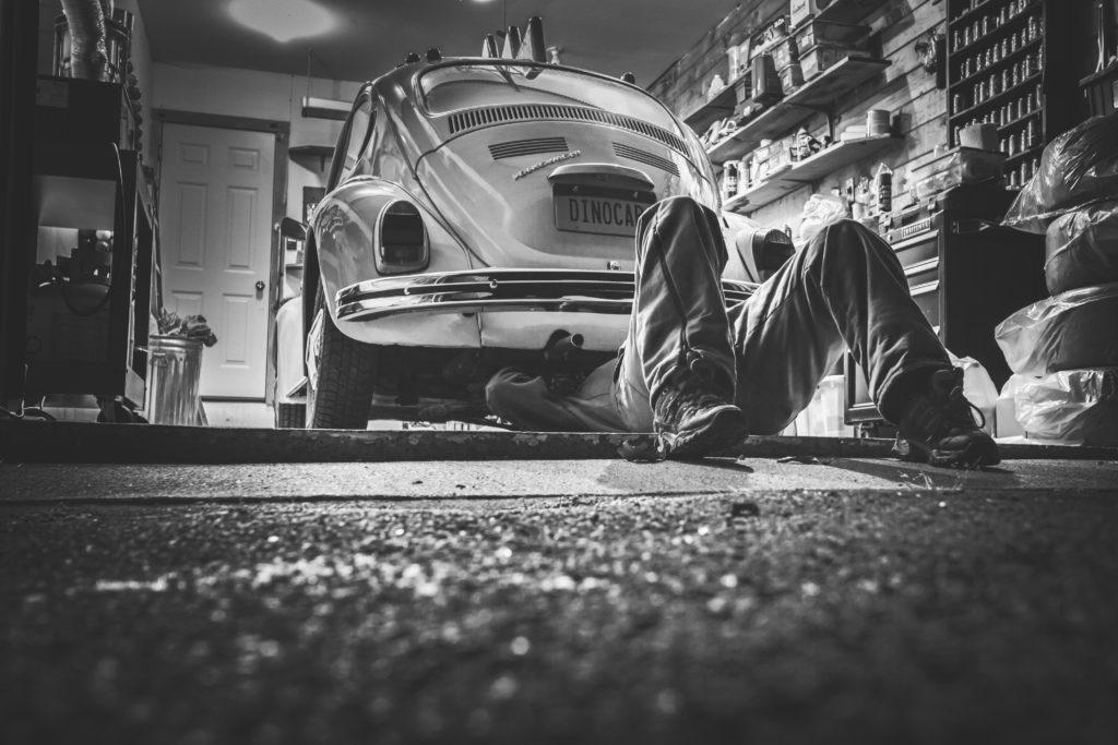 En person lagar bilens avgasrör